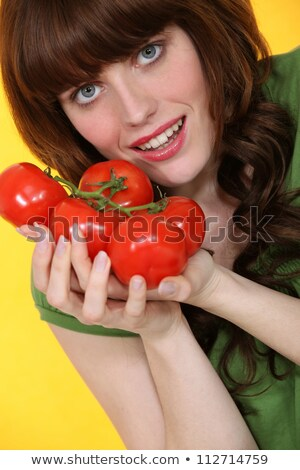Stock photo: portrait of red-haired girl posing with bunches of tomatoes