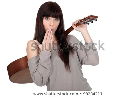 young woman carrying guitar over shoulder with hand before mouth stock photo © photography33