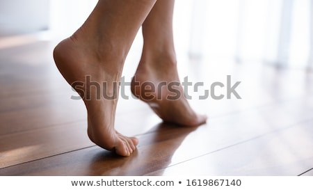 Slender young woman relaxing barefoot on the floor Stock photo © dash