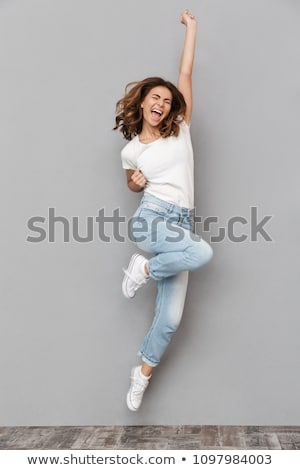 Full-length portrait of a young cheerful woman on gray background Stock photo © deandrobot