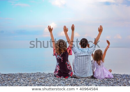 Happy family with little girl sitting on stony beach lifted hand Stock photo © Paha_L