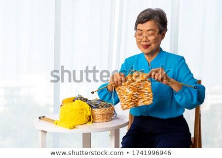 Elderly grandmother sitting knitting in a chair Stock photo © ozgur