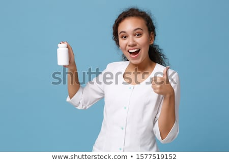 Woman holding bottle with pills and showing thumb up Stock photo © deandrobot