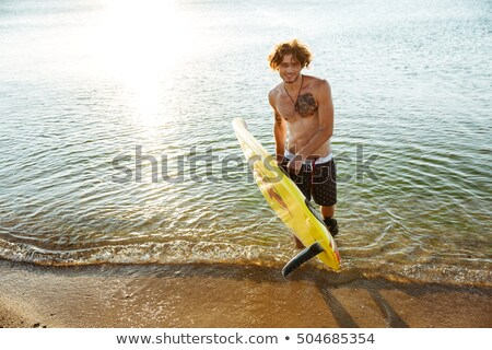 Smiling curly man holding his surf board at the beach Stock photo © deandrobot