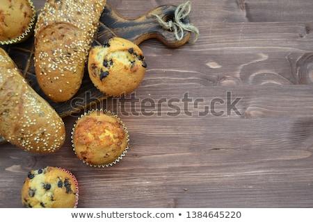 Different fresh bread in wicker basket on rustic table on wooden Stock photo © Yatsenko