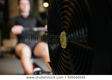 Kas adam kürek çekme makine spor salonu odak Stok fotoğraf © deandrobot