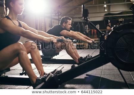 Mulher exercício remo máquina ginásio Foto stock © chesterf
