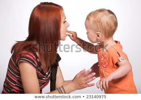 young girl feeding her mother with cake stock photo © is2