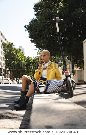 Young woman sitting on curb talking Stock photo © IS2
