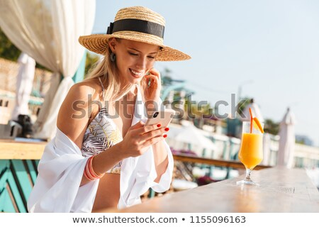 Photo of lovely stunning woman 20s in straw hat smiling and hold Stock photo © deandrobot