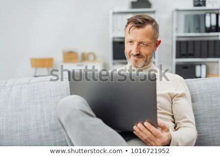 Image of Pleased middle aged business man relaxing Stock photo © deandrobot