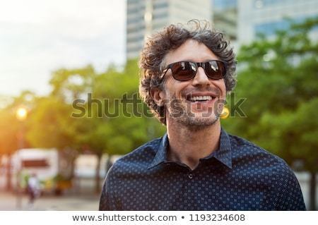 portrait of relaxed casual man wearing sunglasses and blue shirt stock photo © feedough