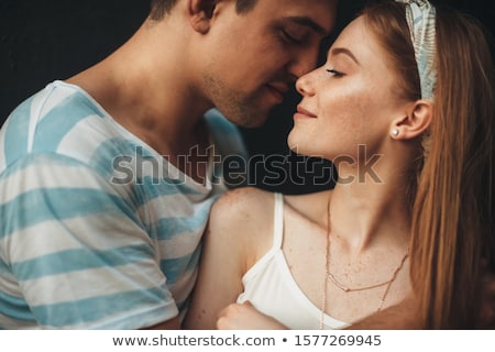 close up side view of a beautiful young couple kissing eyes closed stock photo © deandrobot