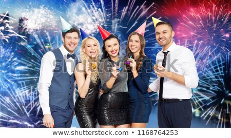 happy friends with party blowers over firework Stock photo © dolgachov