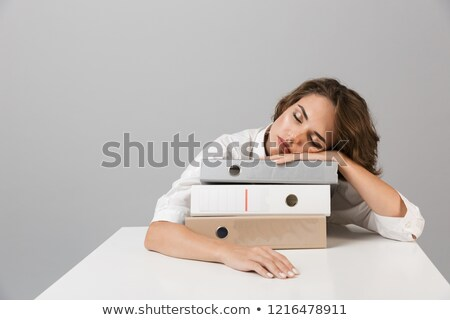 bored tired young woman sitting at the table isolated over grey background sleeping on folders stock photo © deandrobot
