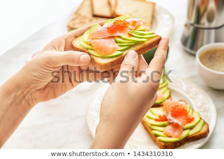 Woman's hand holds healthy sandwich from fresh seafood and vegetables on a light background. Stock photo © artjazz