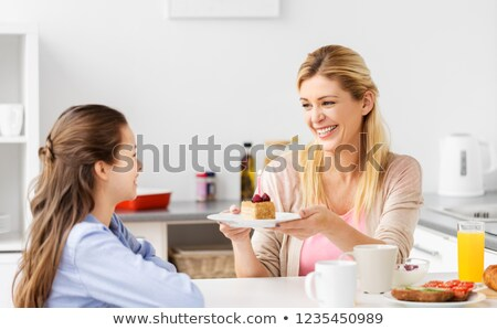 mother giving daughter piece of birthday cake Stock photo © dolgachov