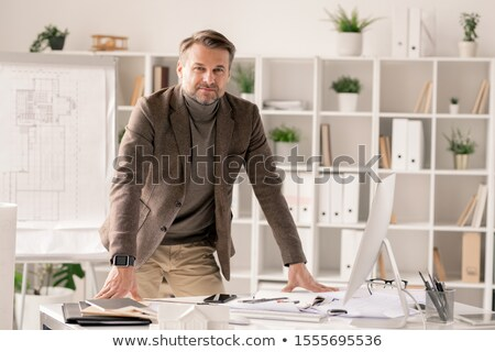 successful and confident architect in formalwear bending over desk in office stock photo © pressmaster