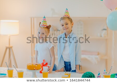 Indoor shot of small girl and boy wear party hats, stand near festive table with cake, paper cups an Stock photo © vkstudio