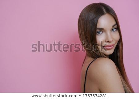 Portrait of beautiful woman with straight dark hair, clean skin, stands sideways shows bare shoulder Stock photo © vkstudio