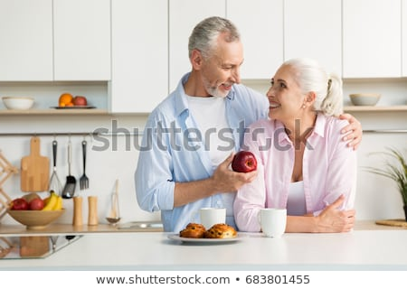 a couple in the kitchen, the man is eating an apple Stock photo © photography33