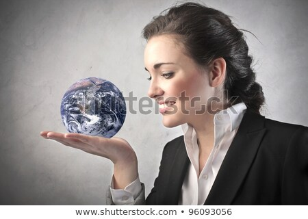 Stock photo: Young businesswoman with the world in her hands