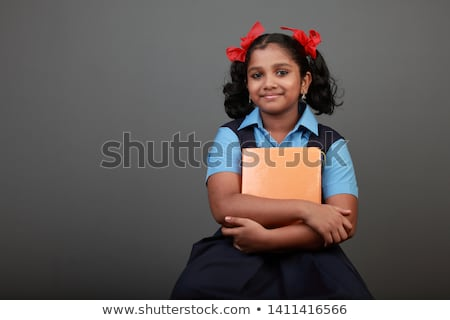 cute school kid holding notebook and reading stock photo © stockyimages