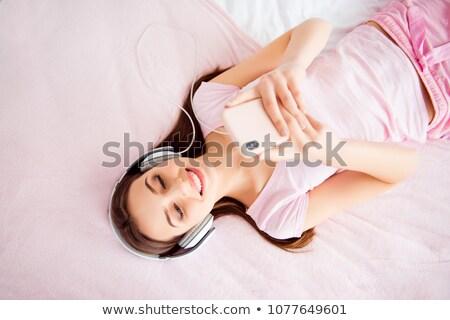 Mooie jong meisje hoofdtelefoon witte bed zilver Stockfoto © gromovataya