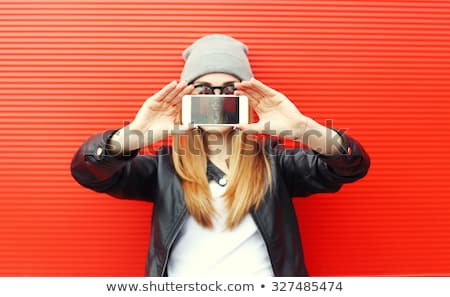 Stylish young female taking a photo with cellphone stock photo © pablocalvog