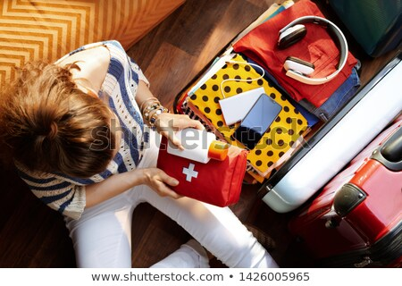 woman preparing for vacation with suitcase on white stock photo © elnur