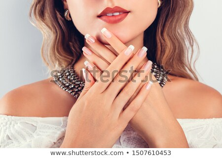 beauty portrait of a young woman showing her manicure stock photo © deandrobot