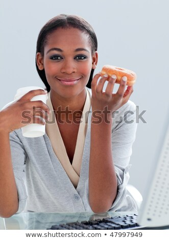 Woman drinking coffee and eating donnut Stock photo © wavebreak_media