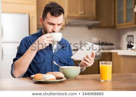Man sipping coffee and reading tablet computer Stock photo © ozgur