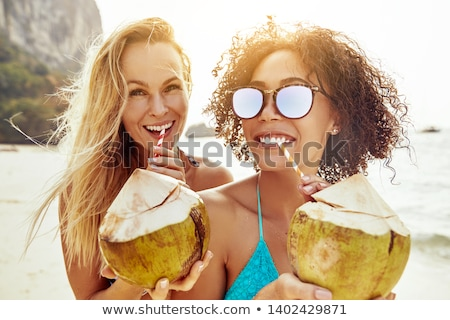 Smiling young woman sipping a coconut cocktail Stock photo © dash