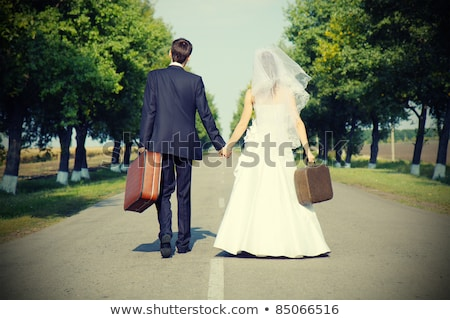 woman holding suitcase on countryside road stock photo © nobilior