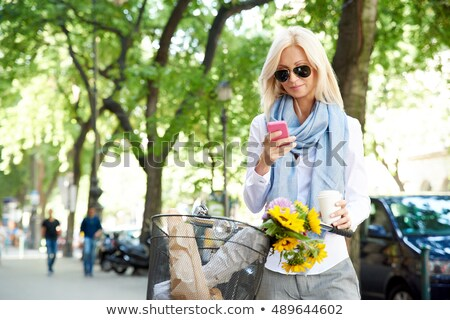 Woman texting on phone while riding bicycle Stock photo © stevanovicigor