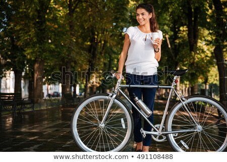 Smiling young woman drinking takeaway coffee and holding bicycle Stock photo © deandrobot