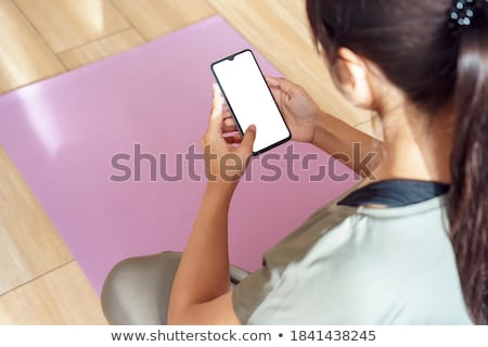 woman doing yoga and using cell phone sitting on mat stock photo © deandrobot