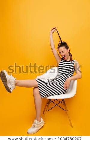 dziewczyna · włosy · stwarzające · posiedzenia · krzesło - zdjęcia stock © deandrobot