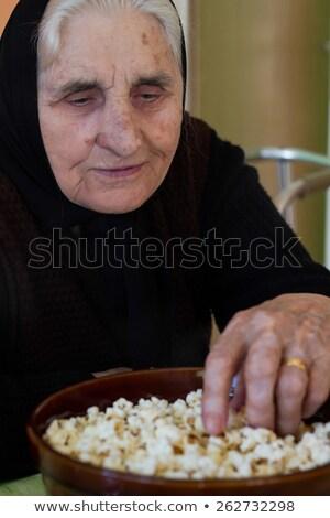 Függőleges kép töprengő nő eszik pattogatott kukorica Stock fotó © deandrobot