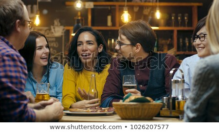 Smiling woman using mobile phone while having a glass of beer in restaurant Stock photo © wavebreak_media