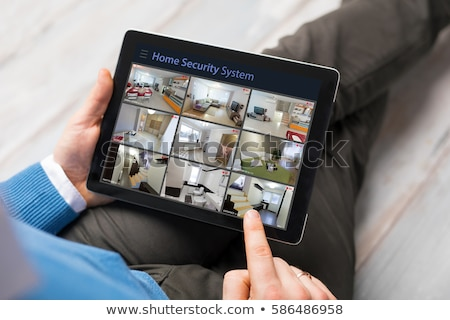 Stock photo: Person Looking At Home Security Cameras On Laptop