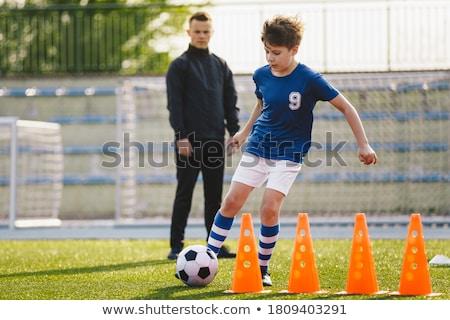 Soccer player dribbling through cones Stock photo © wavebreak_media