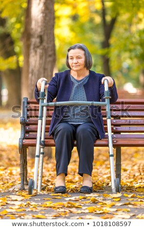 Senior woman with walker getting up and walking outdoors Stock photo © manaemedia