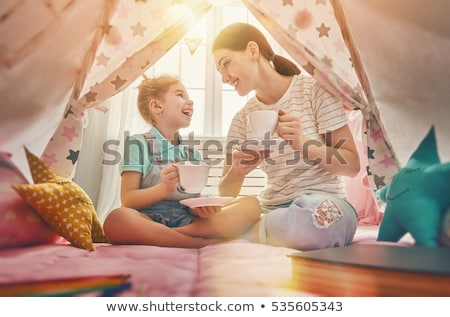 Young woman having tea party in small room Stock photo © IS2