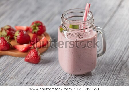 milk smoothie with strawberries mint leaves and chia seeds in a glass jar with a straw on a wooden stock photo © artjazz