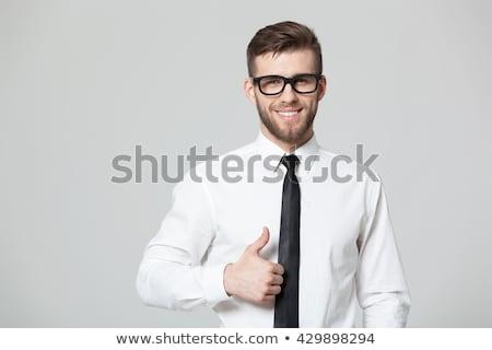 portrait of confident handsome businessman showing sign on black background stock photo © traimak