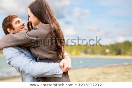 happy couple hugging over autumn beach stock photo © dolgachov