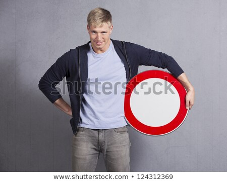 Smiling man holding universal forbidden sign. Stock photo © lichtmeister