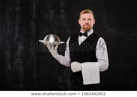 Happy elegant waiter of classy restaurant holding towel and cloche with food Stock photo © pressmaster